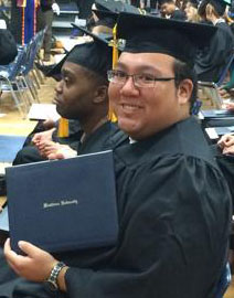 Marcus at his graduation, wearing cap and gown, holding his diploma
