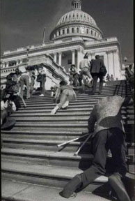 Black and white photo of various people climbing up the steps of a Capital building