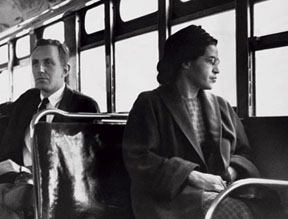 Rosa Parks sitting on a bus with a white man sitting behind her