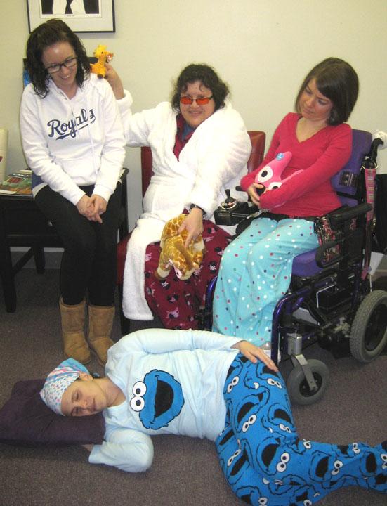 KYEA staff, dressed in pajamas, look down at Julia sleeping on the floor