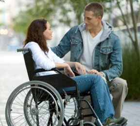 Guy speaking to a girl who is wheelchair mobile