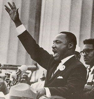 Martin Luther King Jr boldly speaking with his hand in the air