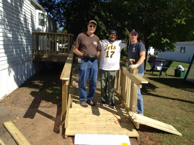 threee people on wooden ramp that is nearly complete