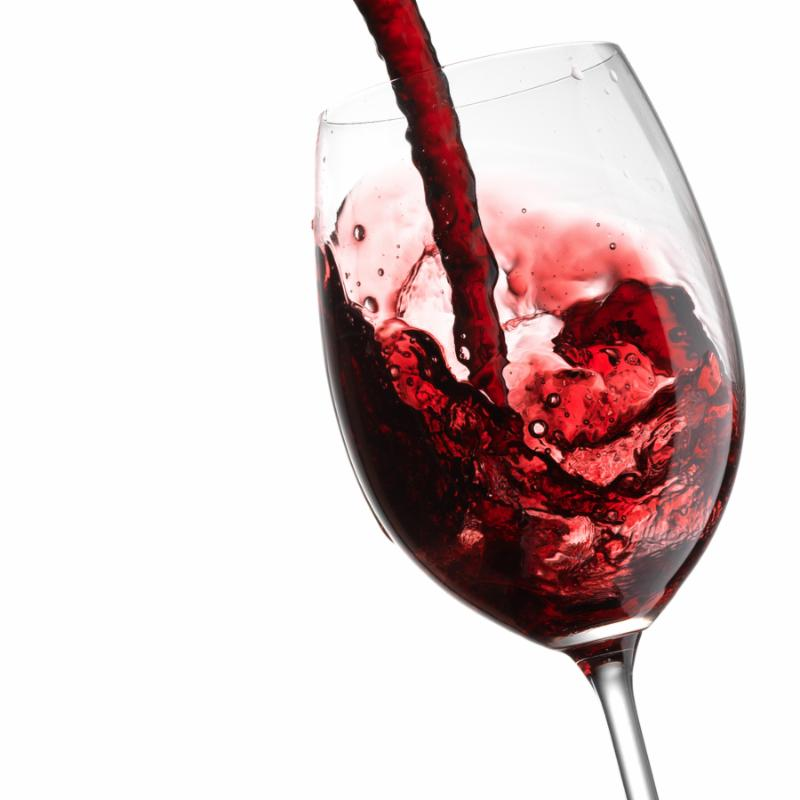 Red Wine Pouring with splashes into wine glass