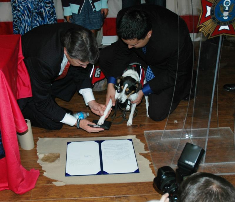 at governor's press conference, Adan's dog Bootz gives paw print of approval on new service animal legislation