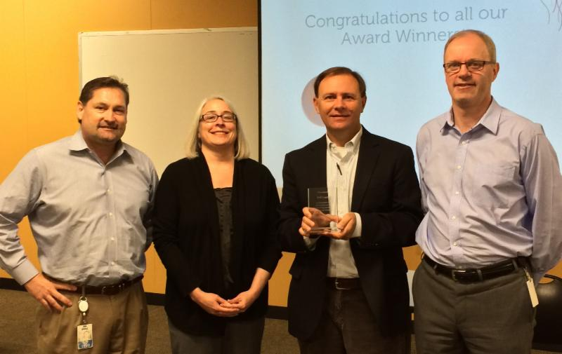 photo of DRTx attorney gives award to Dell attorneys for pro-bono work for children