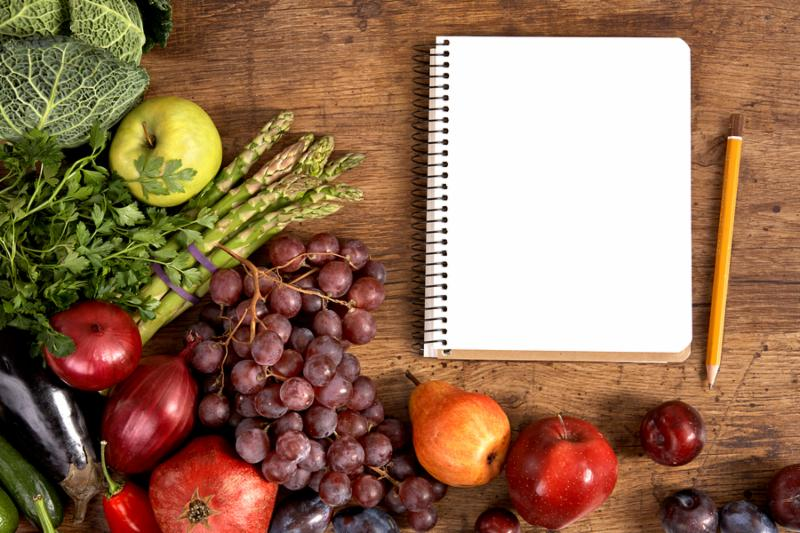 studio photography of open blank ring bound notebook surrounded by a fresh vegetables and pencil on old wooden table