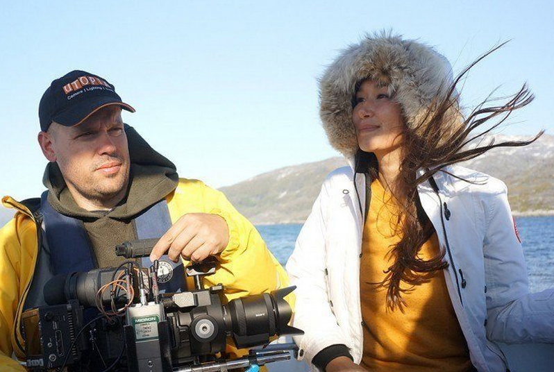 A videographer sits besides an Inuit woman as their boat speeds over open Arctic waters.