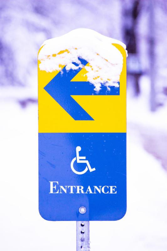 Blue and yellow sign pointing the way towards an accessible entrance.