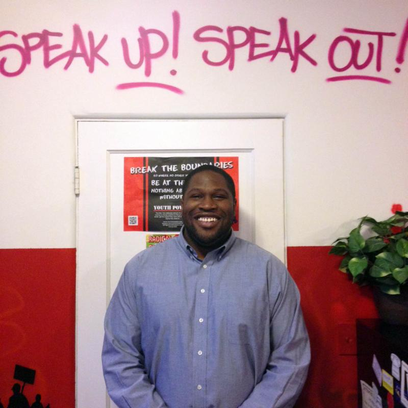 Alex stands smiling in front of the words speak-up speak out painted on the YP! office wall