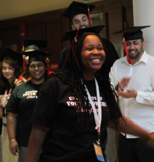 A young lady walks wearing a cap, UYP class of 2014 shirt and a big smile. Fellow students stand behind her clapping and smiling.