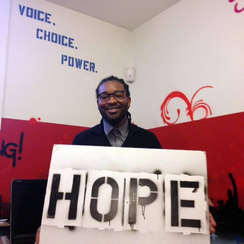 Kevin stands holding the hope sign and smiling in front of the words Voice Choice Power painted on the YP! office walls