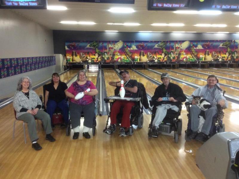Grande Prairie Peer Program members share a laugh while bowling.