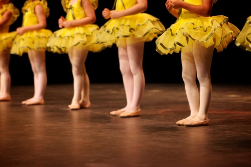 Dancers on stage during a recital in bright costumes. Noise reduction was applied on the floor and