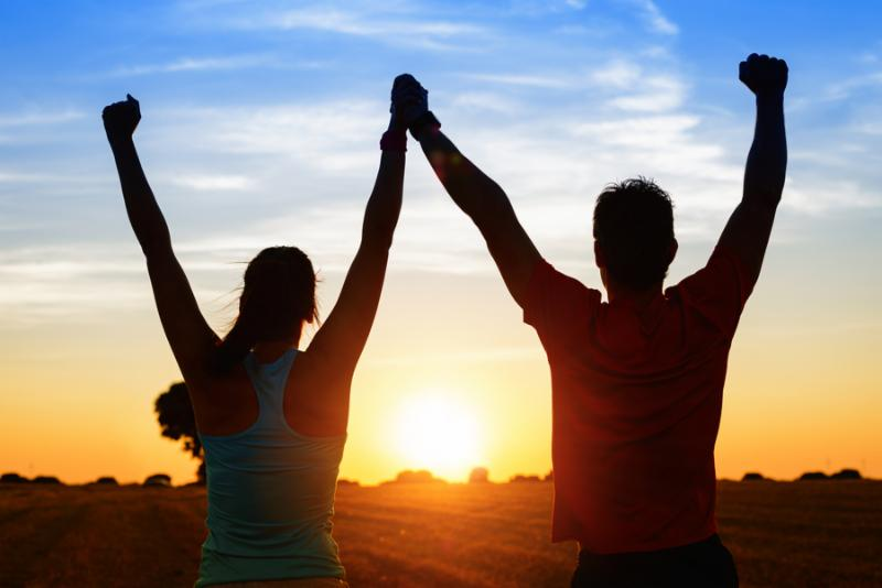 Successful couple of young athletes raising arms to golden summer sunset sky after training....
