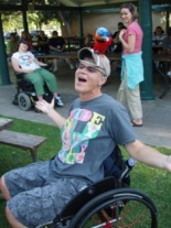 Young man in wheelchair smiling with arms outstretched at a park and others in background