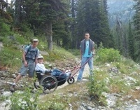 Family hiking with a trail buddy for wheelchair access