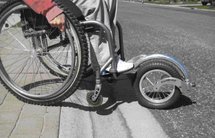 FreeWheel device on a wheelchair moving over a curb