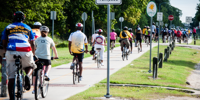 Cyclists ride on a separated bike path.