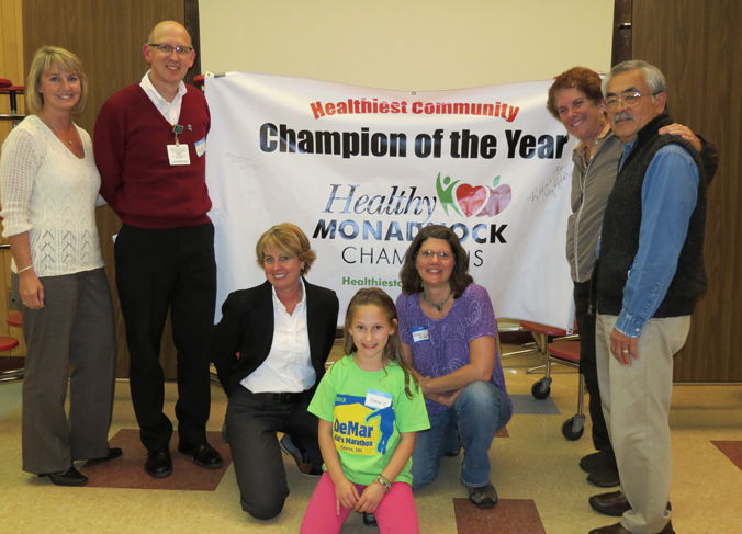 Jen Risley accepts Healthiest Community Champion of the Year award with last year's winners, Elm City Rotary Club.