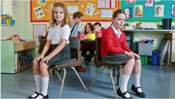 Photo of two schoolchildren sitting, one on a wedge pillow and one on a backward sloping chair. Society of Teachers of the Alexander Technique