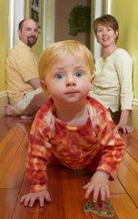 baby in pajamas crawling hallway