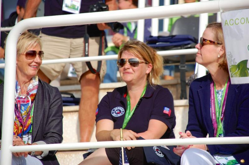 USEF president Chrystine Tauber (left) and USET Foundation executive director Bonnie Jenkins (right) take in WEG para-dressage freestyles with 2014 U.S. WEG competitor Susan Treabess. CREDIT: Jennifer Bryant