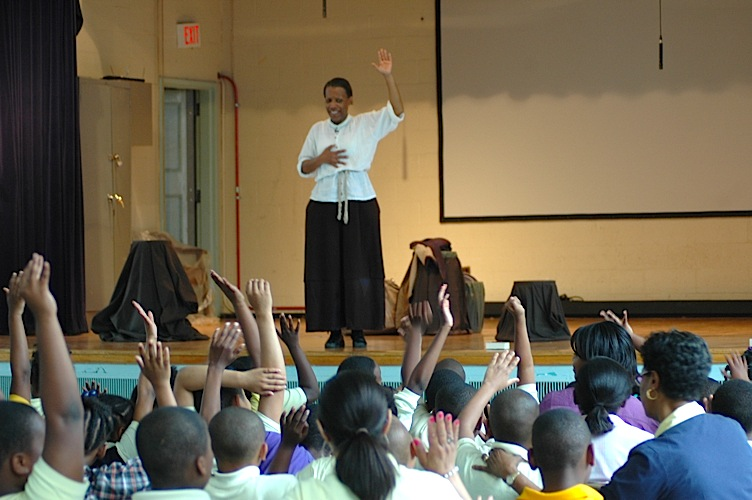 Photo of children raising hands to ask questions during in school performance.