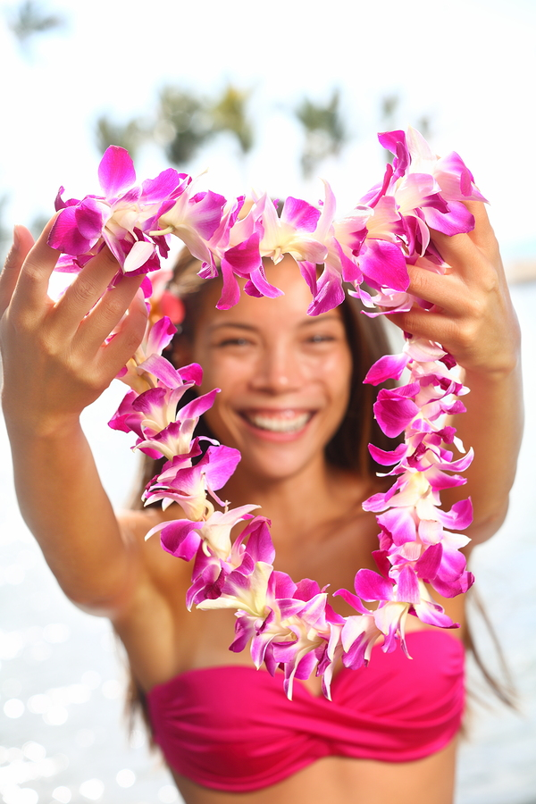 Hawaii woman showing flower lei garland of pink orchids. Beautiful smiling mixed race woman in...