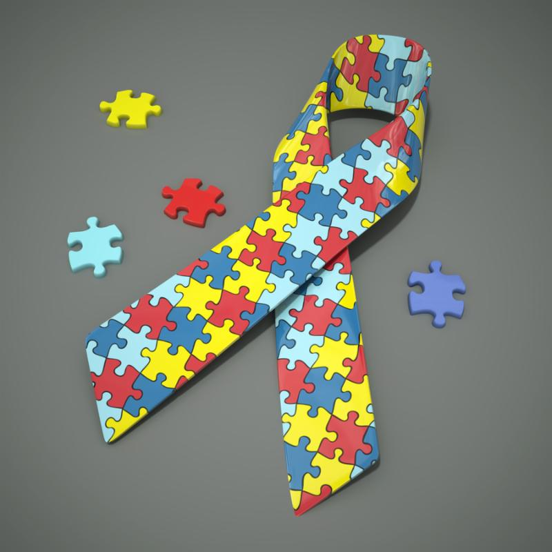 A 3d rendered autism awareness ribbon with colored puzzle pieces.      Clipping path included for the ribbon and puzzle pieces.