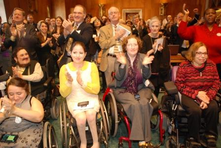 A large groups of people, many in wheelchairs, applaud