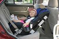 Child in a rear-facing car seat.