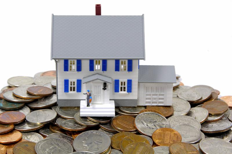 miniature house on top of change.  home savings and lon concept.  see portfolio for similar concepts