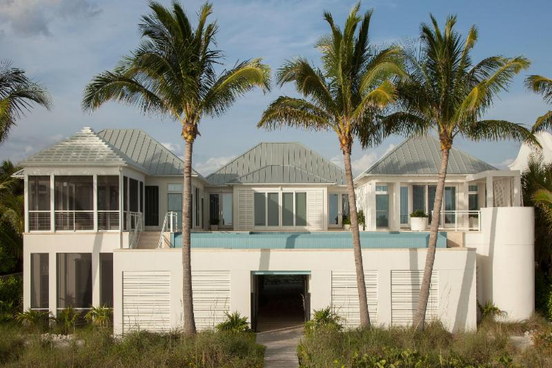 The house and contemporary styled pool are built on pilings 14 feet above the existing flood grade. Under the pool are a dedicated equipment room, bathroom and walk-thru (from the front of the house to the beach). The goal was to build the pool so that there would be no seepage issues to the rooms below the pool. To ensure consistency and a warm sanitized pool/spa when the client is in town a heat pump plus a gas heater, and 2 salt chlorine generators were installed.