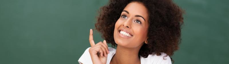 Cute African American woman with an inspired idea lifting her finger in excitement as she sits daydreaming in the classroom during college class