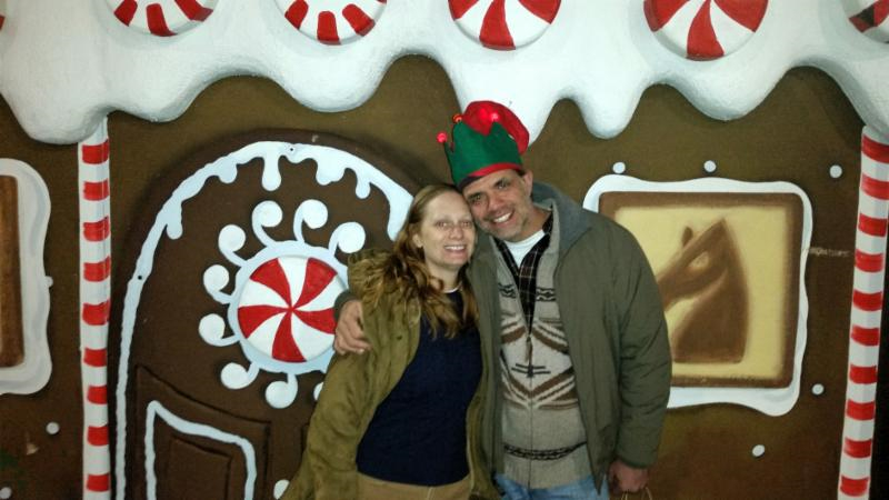 Debbie and Matt standing in front of a Gingerbread House.