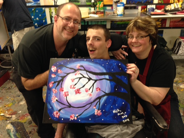 Nick holds his painting with Julie and his dad. The painting is a tree with the moon behind it.