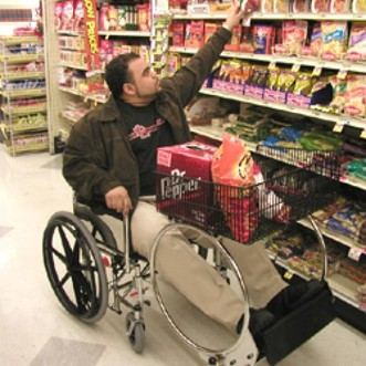 Man in a wheelchair in the grocery store reaching for an item on the shelf