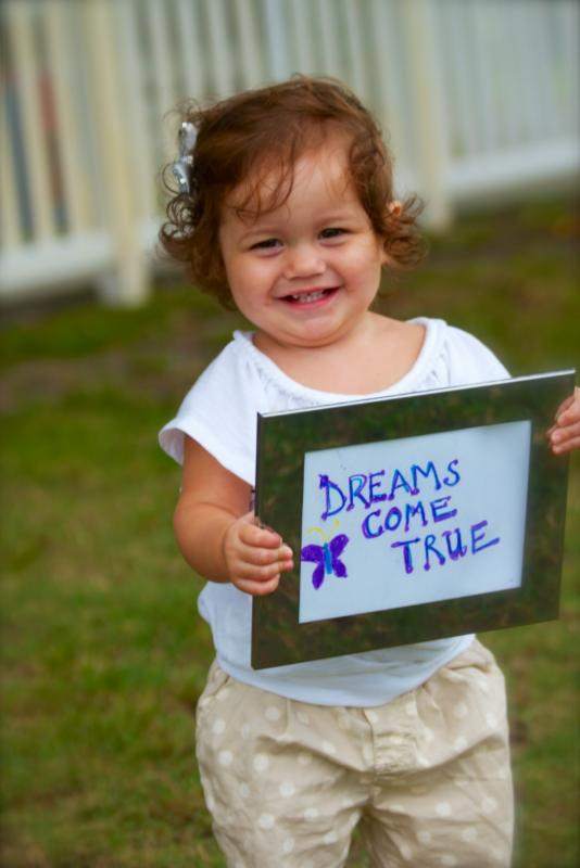 A little girl at Broward Children's Center smiles and holds a sign that reads dreams come true.