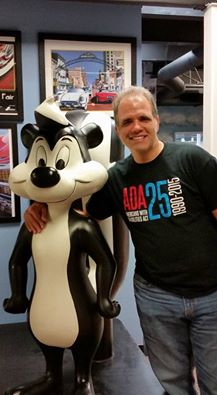 Matt posing with a statue of pepe le pew