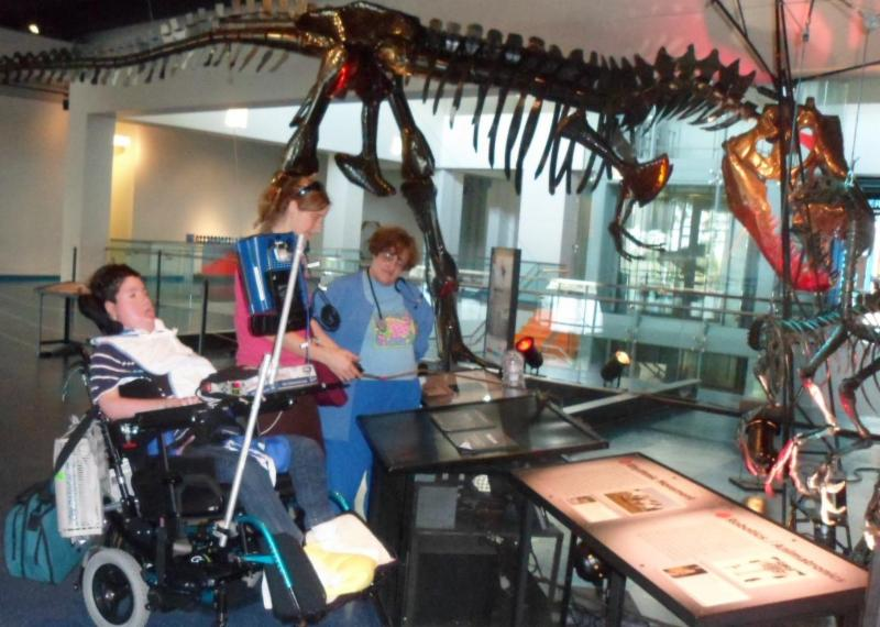 Members of Broward Children's Center visit a museum and observe a dinosaur skeleton.