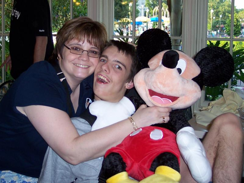 Julie, Nick, and a giant Mickey Mouse stuffed animal.