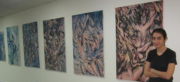 Luisa standing in front of her art work.
