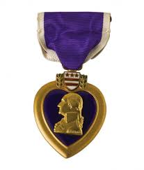 A purple heart medal with a purple ribbon and then a heart shaped medallion hanging off of it.