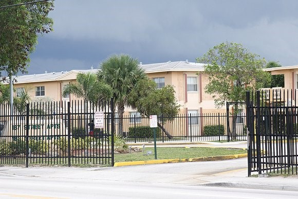 Picture of the outside of a housing development in South Florida.  There are black metal gates surrounding a two story building.