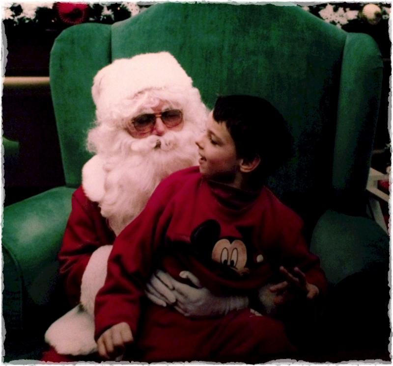 Nick sitting on Santa's lap and smiling