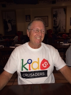 Lester Langer sitting at a table smiling in a Kids Crusaders T-shirt