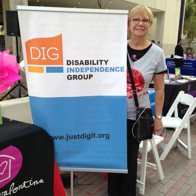 Sharon standing next to the DIG banner at the One Billion Rising Event.