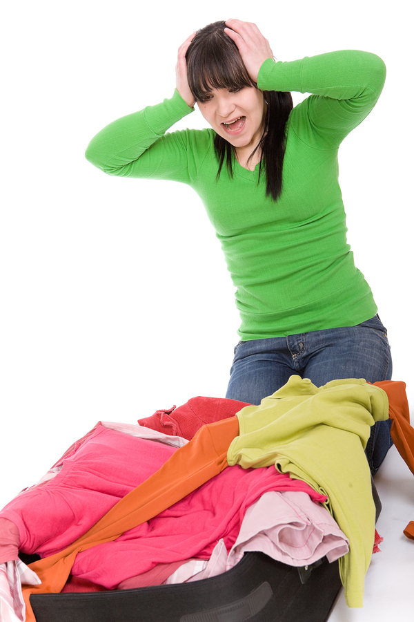 photo of attractive brunette woman packs her clothes.