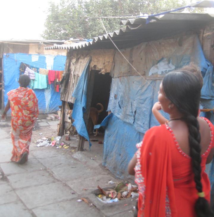 Women walk through a Surat slum